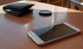 Smartphone en la tabla con la cartera fotos de archivo
