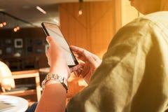 Smartphone en laptop van het jonge mensengebruik in middag, technologie lif royalty-vrije stock fotografie