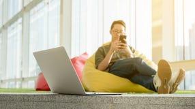 Smartphone en laptop van het jonge mensengebruik in middag, technologie lif royalty-vrije stock foto's