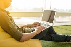 Smartphone en laptop van het jonge mensengebruik in middag, technologie lif royalty-vrije stock afbeeldingen