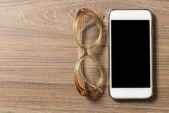 Smartphone en lezingsglazen op een oude houten raad stock fotografie