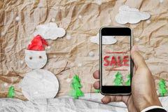 Smartphone en main avec le ` de VENTE de ` sur l'écran, avec le papier chiffonné a coupé le bonhomme de neige en hiver, vente d'a Photo stock