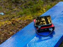Smartphone en powerbank op een raad Stock Afbeelding