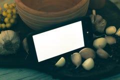 Smartphone en un fondo de madera con las especias Fotos de archivo libres de regalías