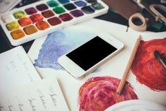 Smartphone en una tabla en el estudio del artista Foto de archivo libre de regalías