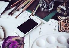 Smartphone en una tabla en el estudio del artista Imagen de archivo libre de regalías