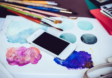 Smartphone en una tabla en el estudio del artista Imágenes de archivo libres de regalías