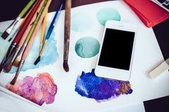 Smartphone en una tabla en el estudio del artista Fotografía de archivo libre de regalías