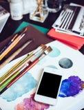 Smartphone en una tabla en el estudio del artista Fotos de archivo libres de regalías