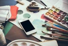 Smartphone en una tabla en el estudio del artista Imagenes de archivo