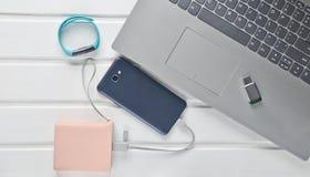 Smartphone, Energiebank, intelligentes Armband, usb-Blitz-Antrieb, Laptop auf einem weißen hölzernen Schreibtisch Beschneidungspf Lizenzfreie Stockfotografie