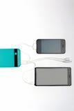 Smartphone está carregando com os entalhes de carregamento do usb do banco dois do poder sobre Foto de Stock Royalty Free