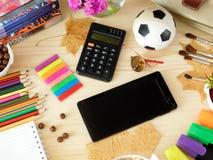 Smartphone et calculatrice entourés par des fournitures scolaires Images libres de droits