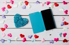 Smartphone et coeur bleu sur une table en bois blanche Photos libres de droits