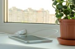 Smartphone et fleur dans un vase sur la fenêtre images libres de droits
