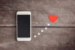 Smartphone et papier de coeurs sur le fond en bois Photos stock