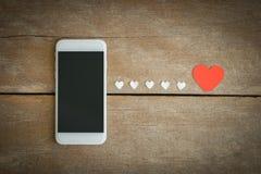 Smartphone et papier de coeurs sur le fond en bois Image stock