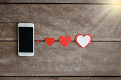 Smartphone et papier de coeurs sur le fond en bois Photo stock