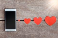 Smartphone et papier de coeurs sur le fond en bois Photographie stock libre de droits