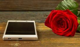 Smartphone et rose de rouge sur une vieille table en bois Image libre de droits