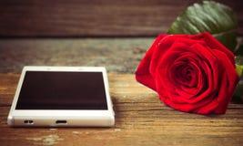 Smartphone et rose de rouge sur une vieille table en bois Images libres de droits