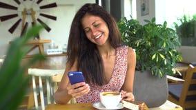 Smartphone et sourire d'utilisation de jeune femme Causerie avec l'ami Image stock