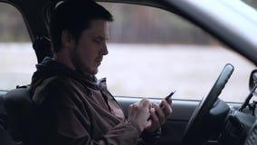 Smartphone europeo del uso del hombre, sentándose en la cabina del coche almacen de video