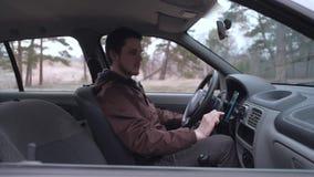 Smartphone europeo del uso del hombre, sent?ndose en la cabina del coche almacen de video