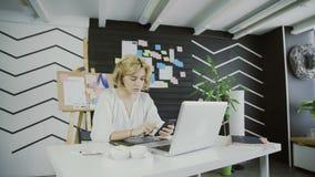 Smartphone fêmea atrativo da terra arrendada do desenhista que senta-se no escritório vídeos de arquivo