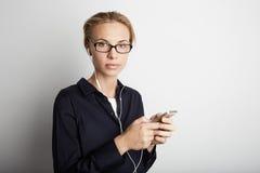 Smartphone för musik för stiliga exponeringsglas för ung kvinna för stående lyssnande tom vit bakgrund för mobil hörlurar Nätt fl Arkivbilder