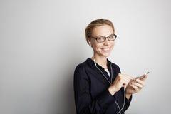Smartphone för musik för stiliga exponeringsglas för ung kvinna för stående lyssnande tom vit bakgrund för mobil hörlurar Nätt fl Arkivfoton