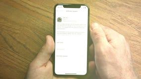 smartphone f?r manPOV-iPhone XS av Apple-datorn som uppdaterar iOS arkivfilmer