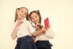 Smartphone f?r selfie f?r tagande f?r flickaskolalikformig Posera som tar det perfekta fotoet Flickaktig fritid roliga flickor ha arkivfoton