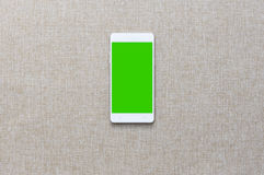 Smartphone with on fabric background, Greenscreen.