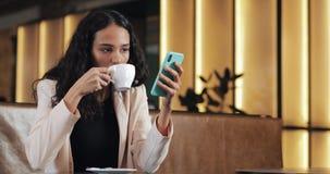 Smartphone feliz del uso de la empresaria y beber el café en café acogedor Freelancer que trabaja en cafetería Trabajo afuera almacen de metraje de vídeo