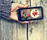 Smartphone in a female hand. display image of strawberry milkshake Healthy Eating Royalty Free Stock Images