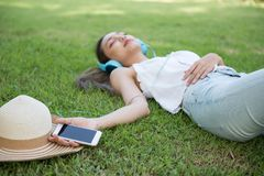 Smartphone on female hand to listen music. Closeup smartphone on hand with young asian woman lying on green field at park. She relax on green meadow to listen Royalty Free Stock Image