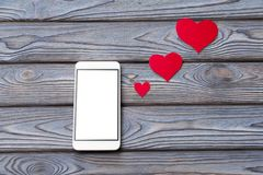 Smartphone, figures of paper in the shape of a heart. On a wooden background. phone call, love. Valentine`s Day. congratulation Stock Image
