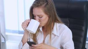 Smartphone flicka som använder app på telefonen som dricker kaffe som i regeringsställning ler Härlig mångkulturell ung tillfälli royaltyfri foto