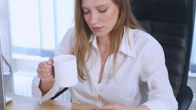 Smartphone flicka som använder app på telefonen som dricker kaffe som i regeringsställning ler Härlig mångkulturell ung tillfälli Royaltyfri Bild