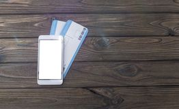 Smartphone, flight tickets, travel. Mobile phone, air tickets. mobile app on a wooden background Royalty Free Stock Images