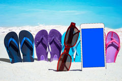 Smartphone and flip flops on the beach Stock Photos