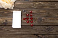 Smartphone, flower, figures of heartsи. Smartphone, flower, figures of hearts on a wooden background. romantics. love. Valentine`s Day Royalty Free Stock Photography