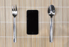 Smartphone with fork and spoon on bamboo mat background Royalty Free Stock Photos