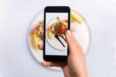 Smartphone-foto van een hoofdgerecht van eendbeen en verse groenten het plaatsen stock afbeelding