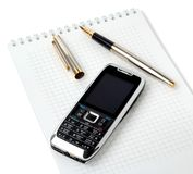 Smartphone and fountain pen lying on a notebook Royalty Free Stock Images