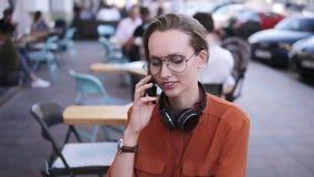Smartphone-Frau, die am Telefon beim Sitzen im Café spricht Sie lächelt Schöne junge Frau, die zufälliges hat stock video