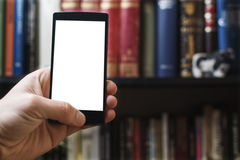 Smartphone in front of book shelf Stock Images