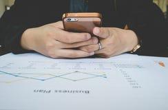 Smartphone Gebrauch der berufstätigen Frau für Arbeit mit Geschäftszusammenfassungs- oder Unternehmensplanbericht mit Diagrammen  Stockfoto