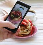 Smartphone geschotene voedselfoto - pannekoeken voor ontbijt met aardbeien Stock Foto's